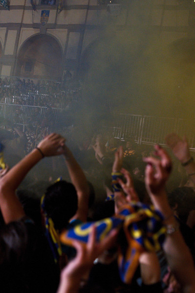 Blue and yellow smoke bombs going off in our standing room fan section