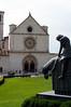 A statue of a weary St Francis of Assisi on the Basilica lawn