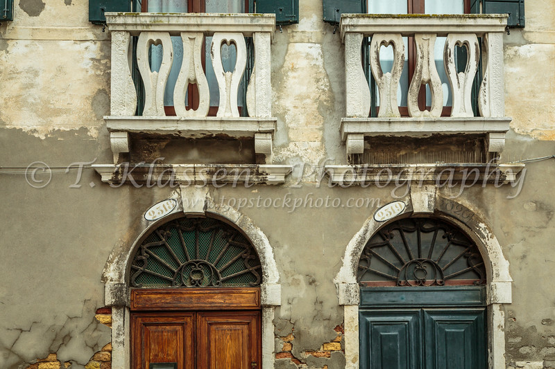 Building door and shuttered windows along a small canal in Veneto, Venice, Italy, Europe.