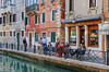 An outdoor cafe beside a picturesque small canal in Venice with boats and small bridges.