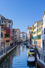 A picturesque small canal in Venice with boats and small bridges.
