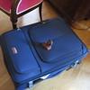 new blue suitcase with broken wheel