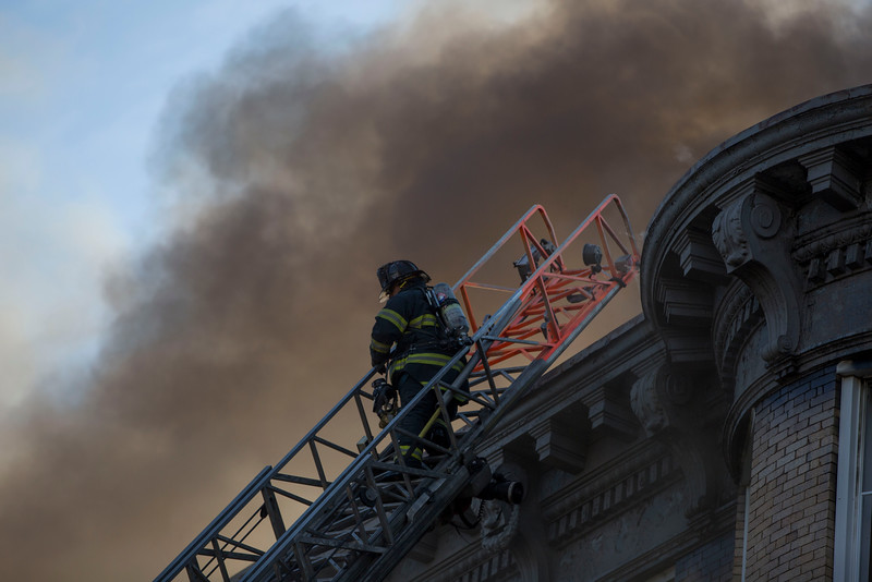 A firefighter climbs a ladder to the roof of 22 West Baltimore St. at a 5-alarm fire in Lynn on Sunday, January 1, 2017. (Scott Eisen/The Item)