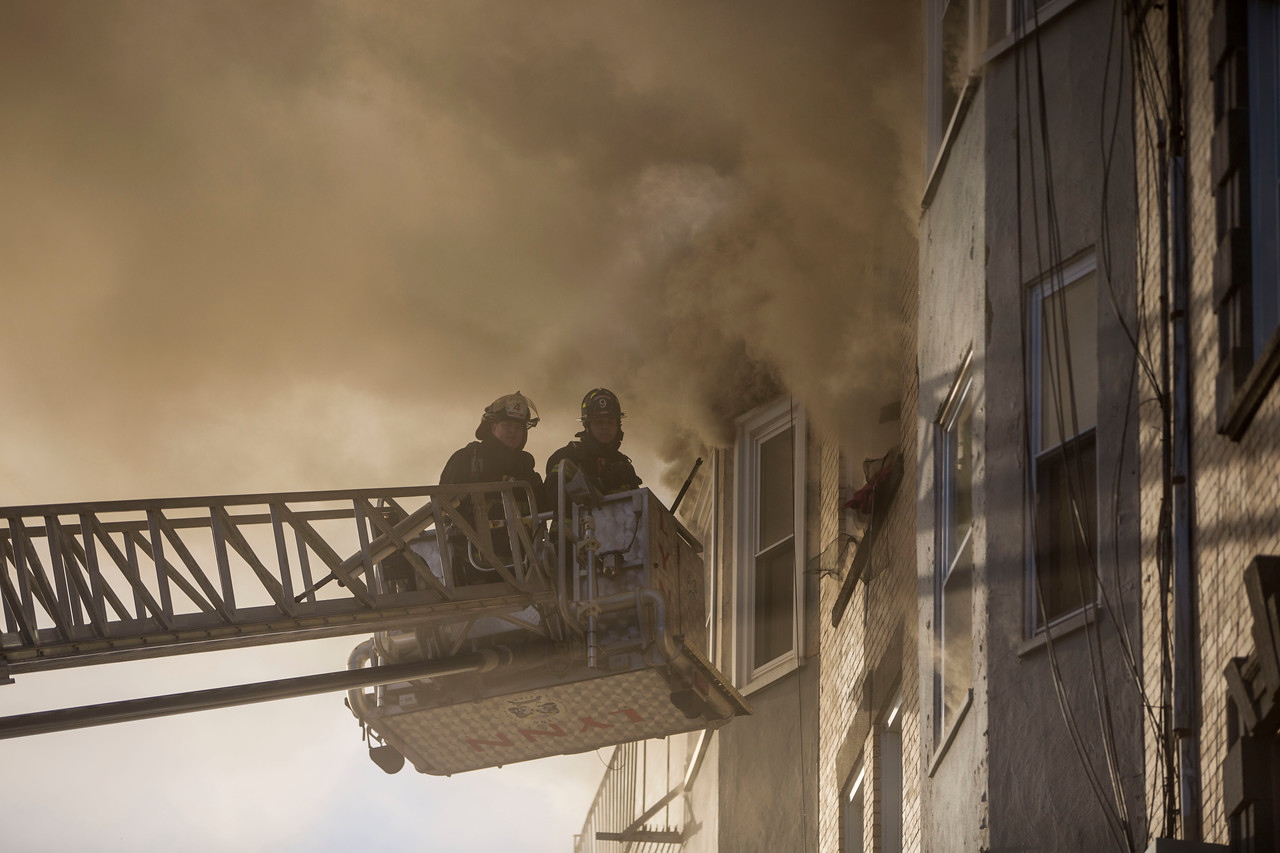 Firefighters on a tower truck at the scene of a 5-alarm fire at 22 West Baltimore St. in Lynn on Sunday, January 1, 2017. (Scott Eisen/The Item)