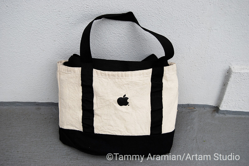 Natural and black canvas tote bag with black web handles and silkscreened black Apple logo on one side. Never used, no flaws, just a little dust from storage. Circa late 1990s/early 2000s. - $85