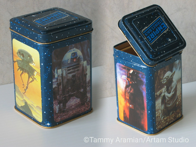 """1980 The Empire Strikes Back upright metal box with hinged lid, logotype on lid and photos on box's sides of R2D2, Darth Vader and Yoda, and McQuarrie concept painting of probe droid. Dimensions (when closed): 2.75"""" wide, 2.75"""" deep, 4.25"""" high. Copyright notice on the bottom: """"TM (c)1980 LFL/Metal Box Ltd. Authorized User. Made in West Germany."""" Near-Mint: nice even coloring with good registration; no rust; back (Yoda) has a very slight indent on the bottom right parallel to the bottom edge which does not affect image; lid opens and closes well; interior is clean. Flaws aren't visible in photo and cannot be seen even in a close-up shot. <br /> $45"""