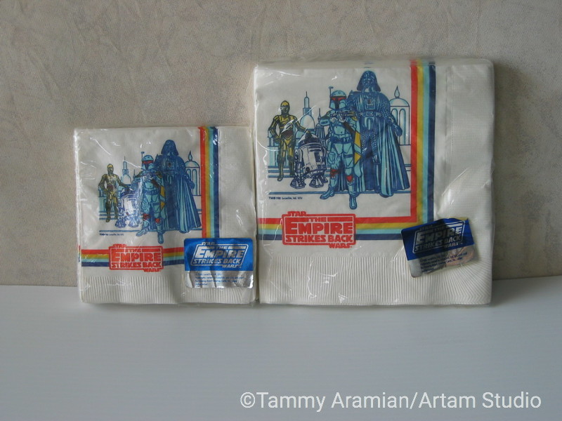 """1980 The Empire Strikes Back three-ply paper napkins by Design Board. One pack of 16 cocktail size (10"""" x 10"""" unfolded) and one pack of 16 lunch size (13"""" x 13"""" unfolded). Both sizes have identical illustration of C3PO, R2D2, Boba Fett and Darth Vader with Bespin background. Both packages still sealed. <br /> $25"""