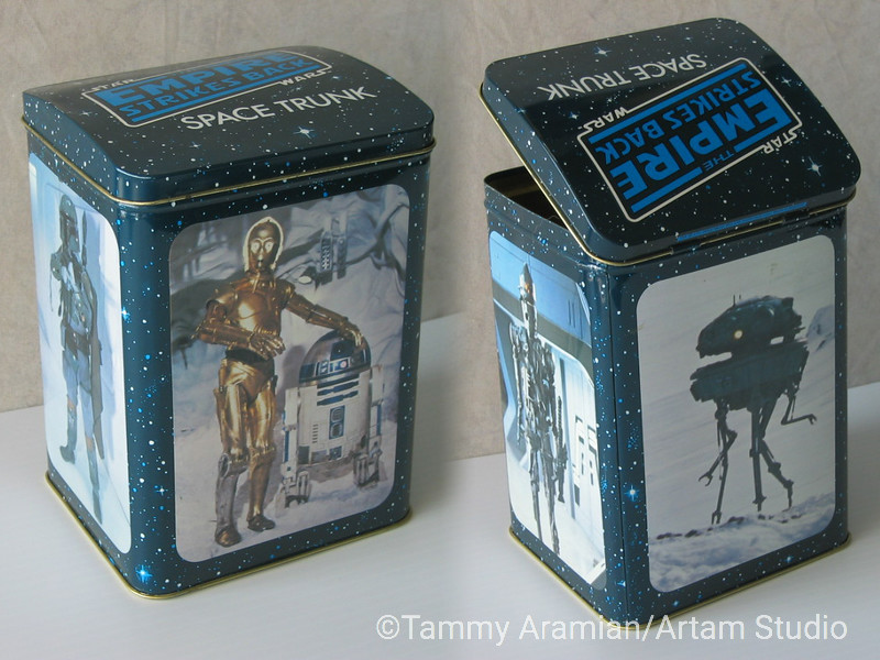 """1980 The Empire Strikes Back metal """"space trunk"""" box with hinged convex lid, logotype on lid and photos on box's sides of R2D2 and C3PO, probe droid, Boba Fett and the robot bounty hunter IG-88. (Isn't it frightening that I remembered IG-88 without looking it up. Damn you George Lucas!) Dimensions (when closed): 5"""" wide, 4.25"""" deep, 7"""" high. Tiny copyright notice on lid's backside reads """"TM (c)1980 LFL/Metal Box Ltd. Authorized User. Made in England."""" Near-Mint: nice even coloring with good registration; no rust; back (Probe Droid) has a pair of horizontal parallel scratches about 1/4"""" wide and some price sticker residue; front (C3PO & R2D2) has one diagonal 3"""" surface scratch which does not affect the image; lid has a very slight indent on the left side parallel to the left edge which does not affect image; lid opens and closes well; interior is clean. Flaws aren't visible in photos and cannot be seen even in a close-up shot.<br /> $75"""
