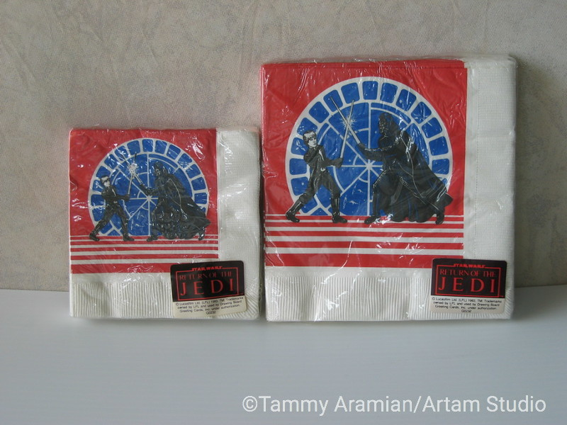 """1983 Return of the Jedi three-ply paper napkins by Design Board. One pack of 16 cocktail size (10"""" x 10"""" unfolded) and one pack of 16 lunch size (13"""" x 13"""" unfolded). Both sizes have identical illustration Luke/Darth Vader duel with Bespin window background. Both packages still sealed. <br /> $25"""