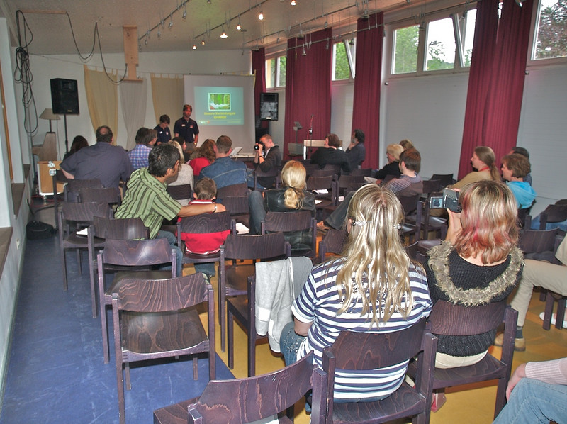 """Ruan and Tina give a presentation on thier 7000km """"charge"""" across Europe - the picture on the screen is the tree hugging one of Cai."""