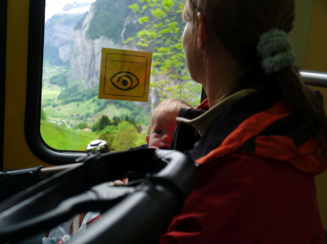 Monday 29th May 2006 - Cai admires the view from the train on the way down from Wengen, he prefers the wall on the other side to the valley with the waterfall.<br /> <br /> We had quite an eventful week, On Monday Cai was very restless all night and although the nurse was there, we could just hear the pump and alarm all night. We were really needing and looking forward to a good nights sleep on Tuesday, when the nurse called to say she was ill and couldn't make it. It was a little more than my body could handle and although we both slept soundly on Wednesday night I picked up a cold and still feel groggy.<br /> <br /> We had planned to have a trial weekend away with Cai, just to see whats possible, some parents in the same situation never leave the house, we however are determined to give him as normal a life as possible.<br /> <br /> We made it okay to wengen and the weather was fine, we caught the train up to wengenalp and then walked back with Cai. It was a bit steep in places but we enjoyed it. Friday night didn't go so well though with Cai beeing awake from 2:30 until 3:30 causing the alarm to go off regularily and the suction pump running which all sounded really loud in the still of the night he had another episode an hour later and needed quite a lot of suction before after and in between. We felt we must have kept the whole building awake and thought it may be best to return home.<br /> <br /> Next morning I bumped into the nice couple (base jumprers) staying in the room opposite ours and sheepishly asked them if we had kept them awake, they replied they hadn't heard a thing, we checked with Angela our hostess and she hadn't had any complaints or heard anything either so we decided to stay. The second night was much better, Cai (and us) slept from 10.30 pm until 8 am with the alarm only sounding a couple of times during the night. (all five of us stayed in the same room).<br /> <br /> but WE DID IT! our first trip away with Cai, now we know we can do it we 