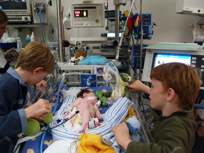 "Friday 11th Nov 05 - Jason and Oiver ""play"" with Cai.<br /> <br /> Cai is now in the other intensive care unit (A) the other one (B) specialised in heart problems. Cai is stable at the moment, he is having some support from the ventilator machine but not a lot.<br /> <br /> The nurse looking after him arrranged for us to visit a little girl about 3 years old who had a tracheotomy  so that we can see what to expect. The little girl seemed happy active and contented as she drew pictures, which made us feel better and gave us more hope for the future.<br /> <br /> later on we were shown the portable home suction unit - I had better get in training if we are to go walking in the mountains with him, but at least hopefully we won't be housebound.<br /> <br /> This Picture should be reassuring to young boys everywhere, that clean disinfected hands doesn't mean you disintegrate.<br /> <br /> Today of course is the 11th day of the 11th month - so we spent some time remembering. I should have been more organised and ordered a poppy for today's photo."