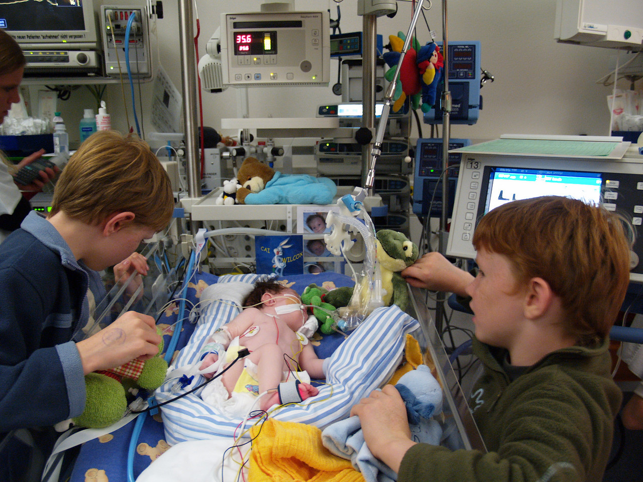 """Friday 11th Nov 05 - Jason and Oiver """"play"""" with Cai.<br /> <br /> Cai is now in the other intensive care unit (A) the other one (B) specialised in heart problems. Cai is stable at the moment, he is having some support from the ventilator machine but not a lot.<br /> <br /> The nurse looking after him arrranged for us to visit a little girl about 3 years old who had a tracheotomy  so that we can see what to expect. The little girl seemed happy active and contented as she drew pictures, which made us feel better and gave us more hope for the future.<br /> <br /> later on we were shown the portable home suction unit - I had better get in training if we are to go walking in the mountains with him, but at least hopefully we won't be housebound.<br /> <br /> This Picture should be reassuring to young boys everywhere, that clean disinfected hands doesn't mean you disintegrate.<br /> <br /> Today of course is the 11th day of the 11th month - so we spent some time remembering. I should have been more organised and ordered a poppy for today's photo."""