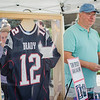 Phil Decisero, of Karen's Closet, sells tickets to win an autographed Tom Brady jersey during the Johnny Appleseed Festival on Saturday afternoon in Leominster. SENTINEL & ENTERPRISE / Ashley Green