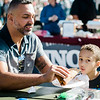 Joel Colon helps four-year-old Anthony enjoy some pizza during the Johnny Appleseed Festival on Saturday afternoon in Leominster. SENTINEL & ENTERPRISE / Ashley Green