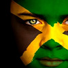 Portrait of a boy with the flag of Jamaica painted on his face.