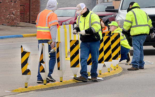 KEVIN HARVISON | Staff photo<br /> Oklahoma Department of Transportation workers repair and replace the protected turn barriers downtown on Carl Albert Parkway recently.