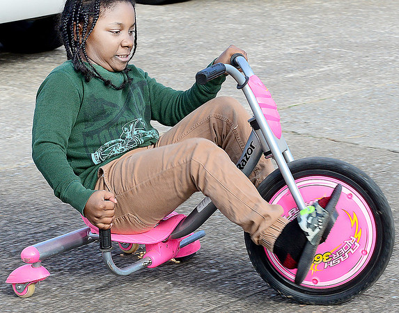 KEVIN HARVISON | Staff photo<br /> Kamary Estwick gets a rolling a little to fast down a driveway so he applies the brakes making the sparks fly on the three wheeler he is riding.