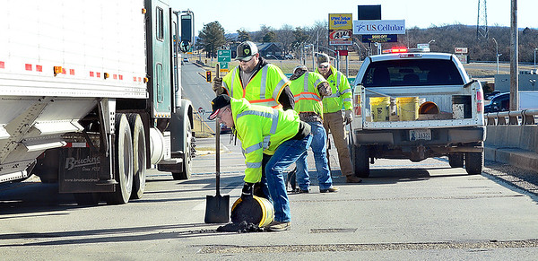 KEVIN HARVISON | Staff photo<br /> Oklahoma Department of Transportation workers put down some asphalt to patch up a bridge on East Carl Albert Parkway.