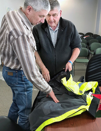 KEVIN HARVISON | Staff photo<br /> Pittsburg County District 3 County Commisioner Ross Selmon, left, looks over a Safety Jacket presented by Tommy Wiley, right, with Advanced Workzone Services. Wiley addressed the board regarding the winter Safety Jackets during a recent Commisioners meeting at the Pittsburg County Courthouse.