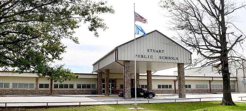 Kevin Harvison | Staff photo  A tattored flag flies in front of Stuart Public School.