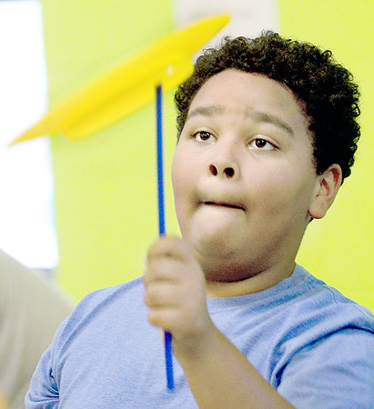 Kevin Harvison | Staff photo<br /> Emerson Elementary student Nazir Hurst tries to keep a plastic plate spinning during a game at the school's carnival.