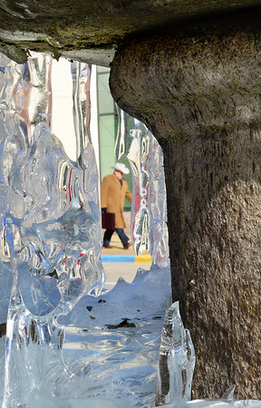 Kevin Harvison   Staff photo<br /> A pedestrian walks by the frozen fountain on Carl Albert Parkway Wednesday as sun and temperatures start to thaw the ice from the fountain.