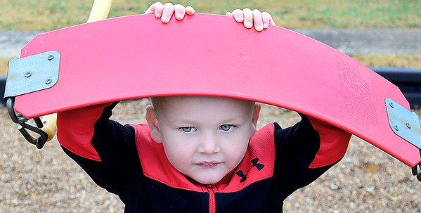 Kevin Harvison | Staff photo<br /> Washington Early Childhood Center/Kibois Headstart student Reid Lauerman rest the swing on his head while look for one of his classmates during recess.