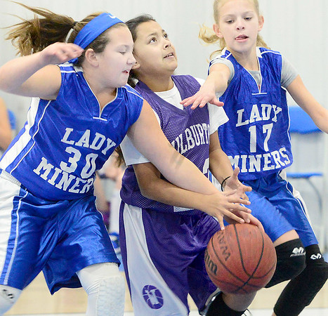 Kevin Harvison | Staff photo<br /> A Wilburton Lady Digger is fouled by a Lady Miner from Hartshorne during fourth grade basketball action at the annual Big Mick Tournment honoring long time Hartshorne coach Mickey Beare. Harthsorne 4th grade girls defeated Wilburton 10-3.