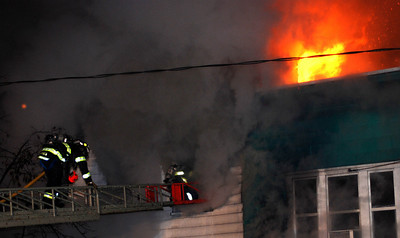 Firefighters climb a ladder to enter a building in an attempt to stop a fast moving fire early Tuesday morning that claimed the lives of two children.