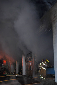 Firefighters battle heavy smoke as they prepare to enter a garage and apartment near the corner of Wylan and Frack streets in West Mahanoy Township Saturday night.