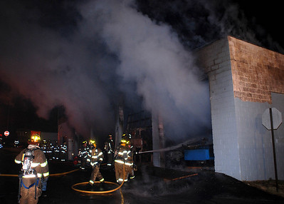 Firefighters battle heavy smoke coming from a garage and apartment near the corner of Wylan and Frack streets in West Mahanoy Township Saturday night.
