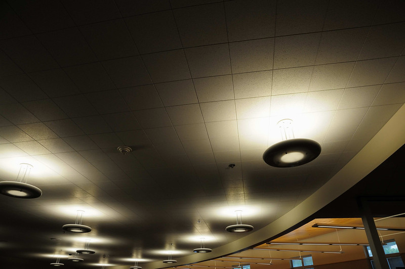 """Light fixtures in library.  These project down as well as up to reflect of ceiling.  Provides a more even light.  These were over the book stacks and the small set of stairs/reading area in the corner.   Library was """"divided"""" into two functional areas - this side with books and reading area.  Other side was tables and computers."""