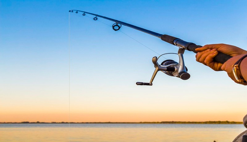 Fisherman fishing rod on the sunset close-up