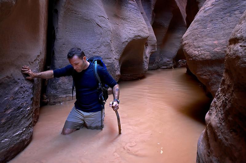 Trekking through the muddy waters of Buckskin Gulch.