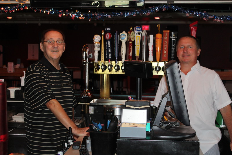 James C. Watson (left) and his son James E. Watson smile behind the bar at J.J. Boomers. The sports bar opened in Lowell in 1997. SUN/Nicole DeFeudis