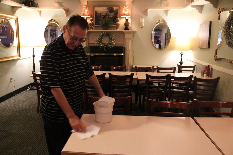 James C. Watson, owner of J.J. Boomers, wipes a table in the dining room. The family is currently considering new locations to reopen after this one closes in December, he said. SUN/Nicole DeFeudis