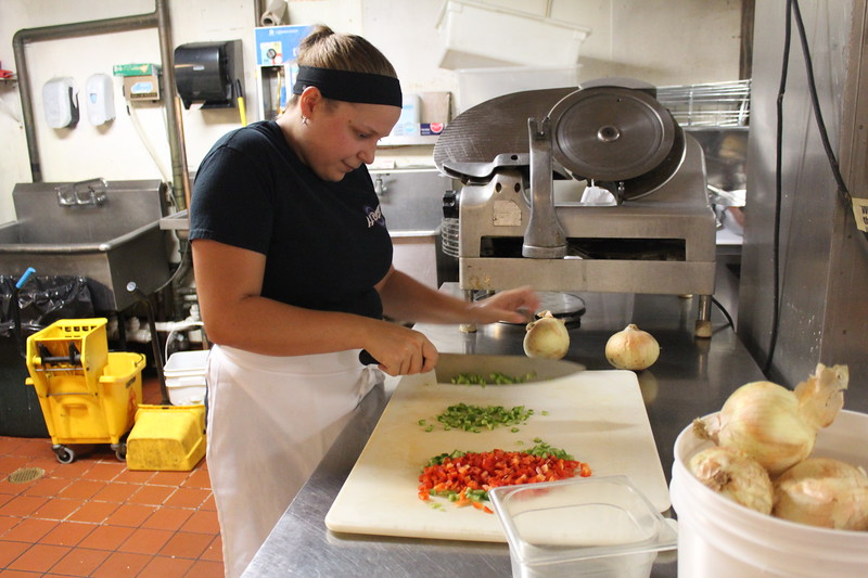 Brieanna Watson, James C. Watson's granddaughter, chops vegetables in the kitchen. SUN/Nicole DeFeudis