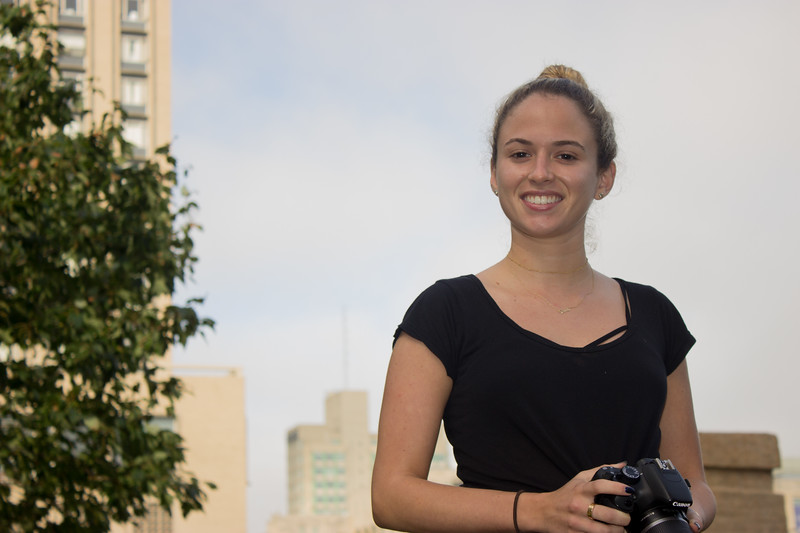 Taylor Ventirce standing on a table on the COM lawn during class September 26, 2017. By using flash, both Taylor and the background are lit well and visible.