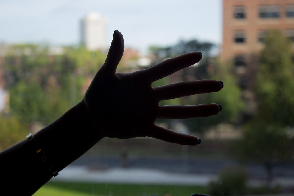 Taylor Ventirce's hand creating a silhouette infront of a window in a COM classroom September 26, 2017 for a class workshop on creating silhouettes.