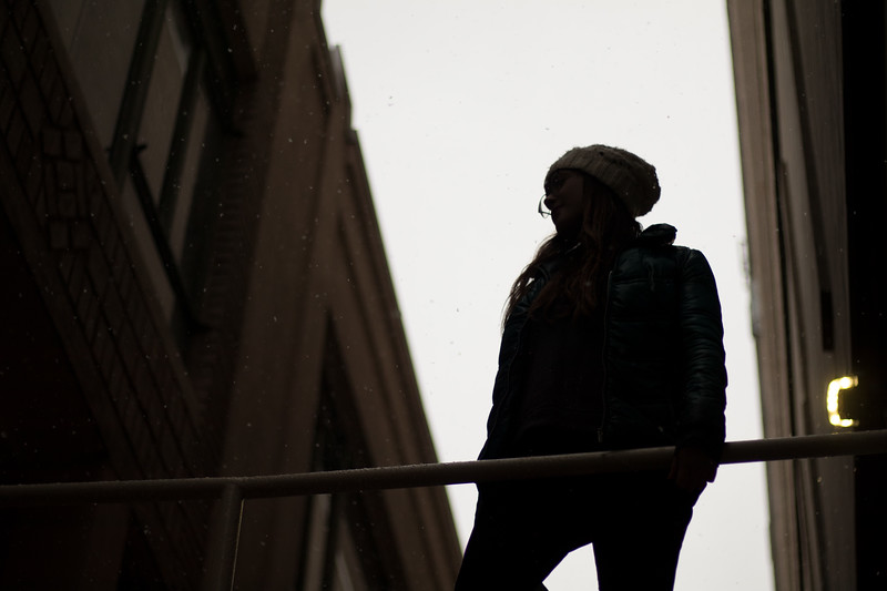 Michaela Shortreid, BU Journalism student, stands on a pedestrian bridge behind Warren Towers on February 22, 2018. She balances on the bottom of a railing to avoid stepping in a puddle of sleet and cigarette butts. Captured by Rachel Callahan.