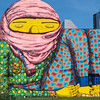 Contrasting colors of The Os Gemeos Boston Mural in South Station.