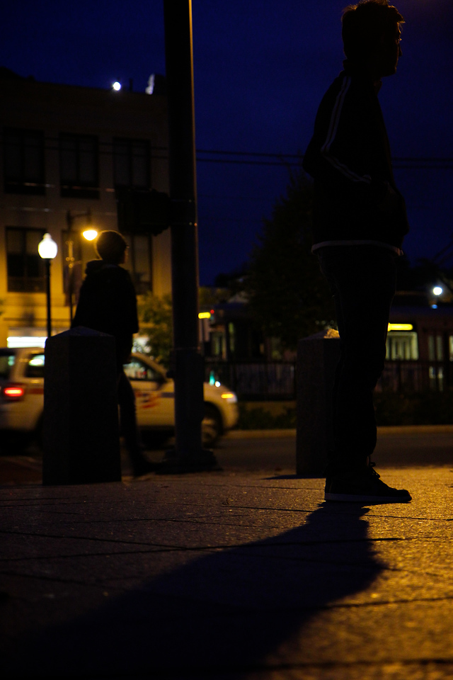 A college student waits for a friend as others pass him by.<br /> <br /> Photo by John Sanderson