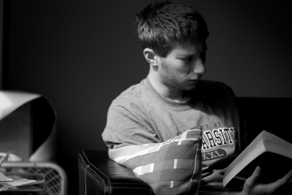 Greg Picker reads a book as light pours in through the windows. Photo by: Conrad Golovac