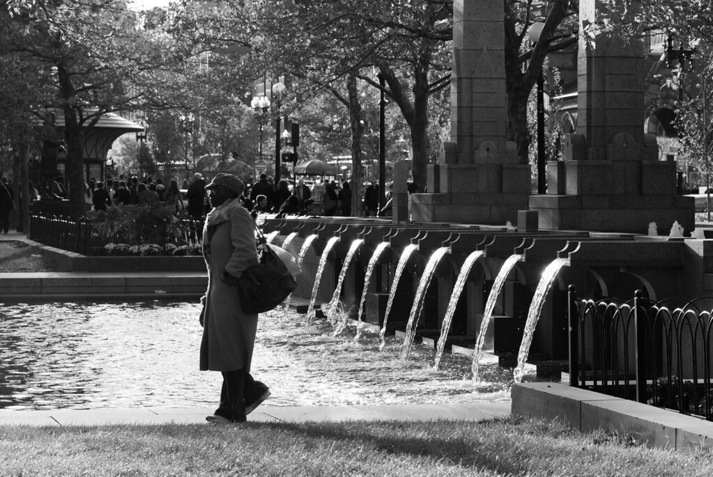 A woman walks next to the fountain in Copley Square in Boston, Mass. on October 13, 2012. Photo by: Roneil Smith