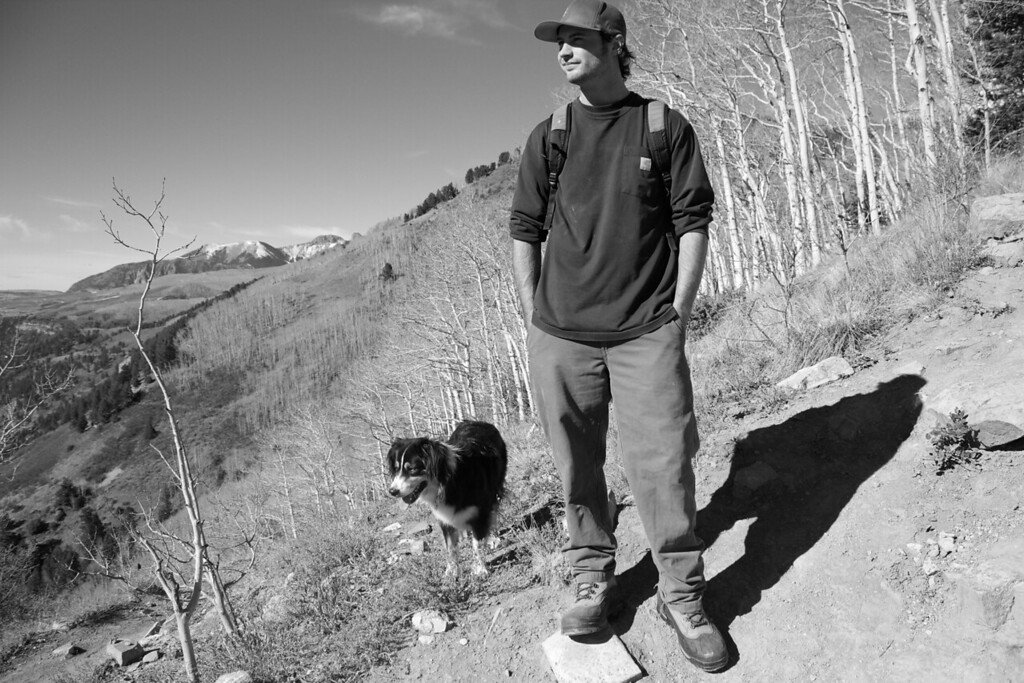 Travis Burnor takes a break with his dog Genevive during a hike up the Judd Wiebe trail in Telluride, CO.