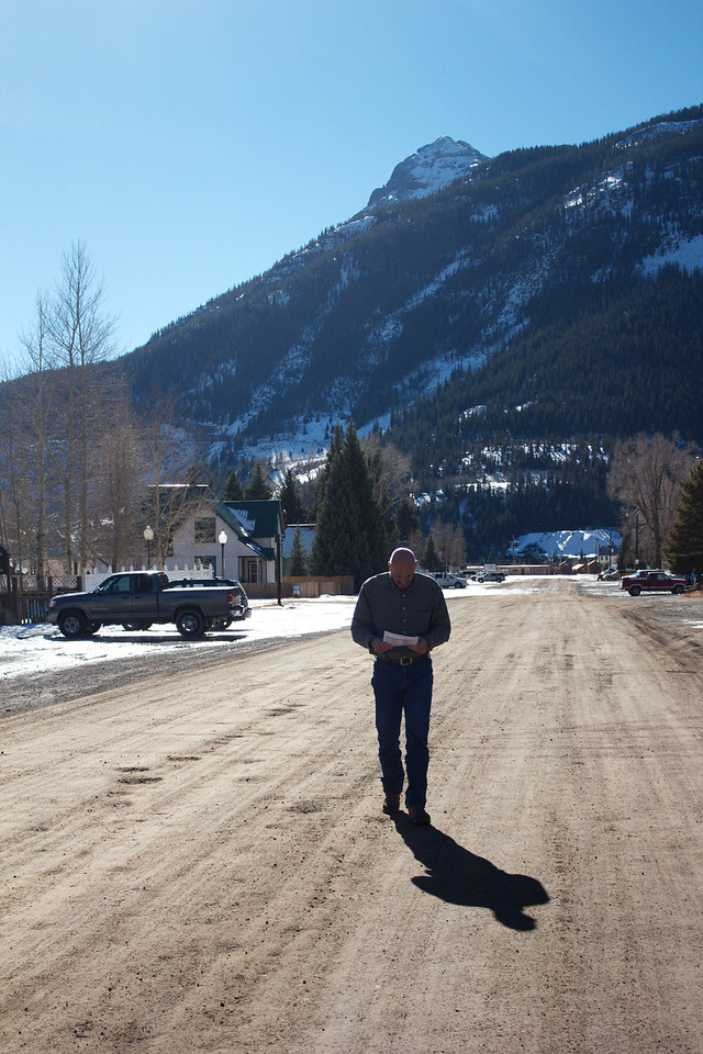 Frank Dority glances at a map while walking down a dirt road in Silverton Colorado.