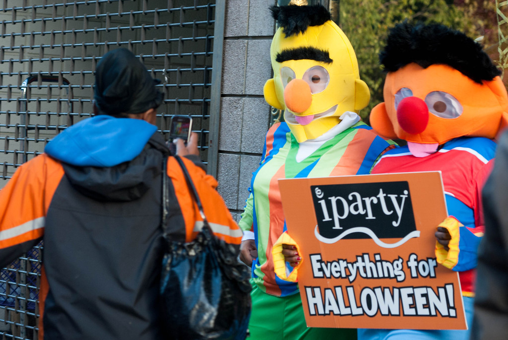 A woman takes a picture of a pair in Bert and Ernie Halloween costumes in front of 365 Boylston Street in Boston, Mass. on October 13, 2012. The costumes were promoting the Halloween store iParty. Photo by: Roneil Smith.