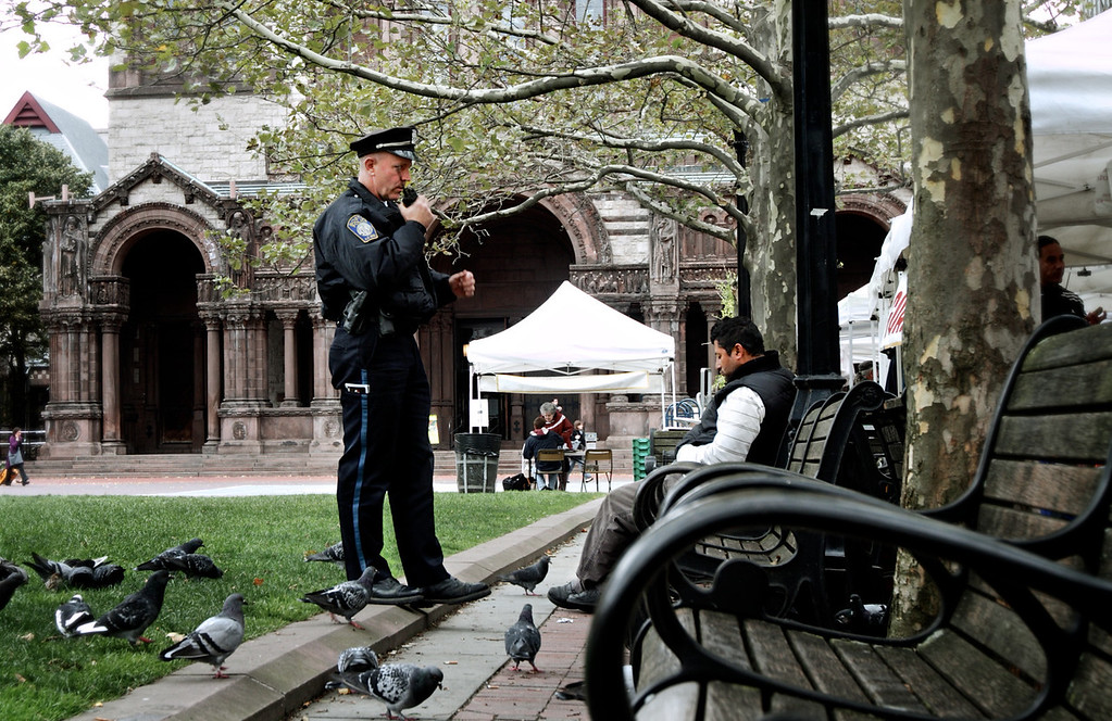 A police officer is concerned with a man who is lost in the park. Copley Sq. Boston, MA Oct, 2012<br /> <br /> Photo by: Yongmyung Yi