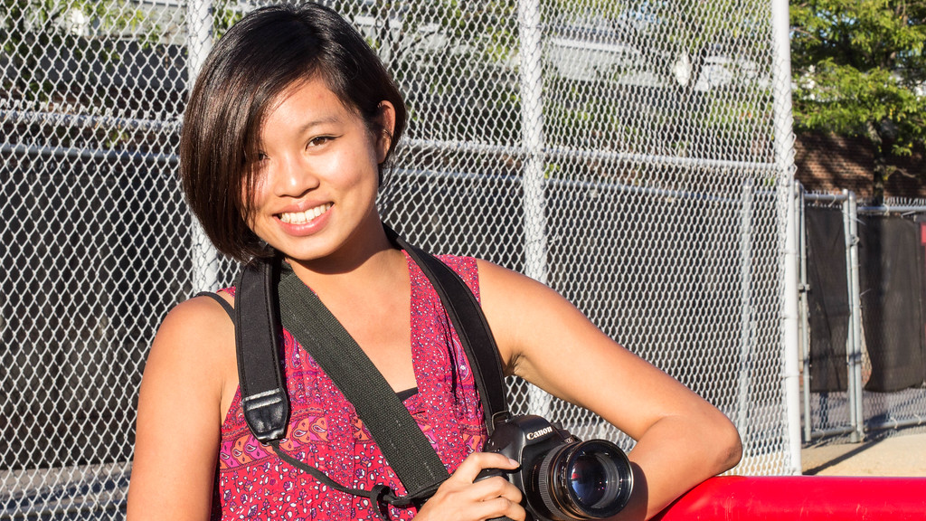 September 12, 2014, Ann Wang, a Boston University graduate photojournalism student, takes a break from taking photos at the BU New Balance Field.